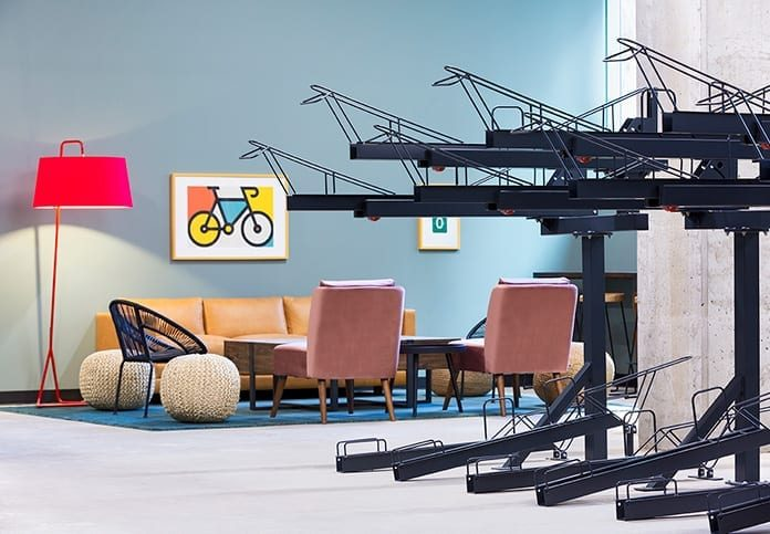 Indoor bike racks with seating in the background