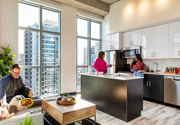 People in apartment with view of kitchen and windows looking out